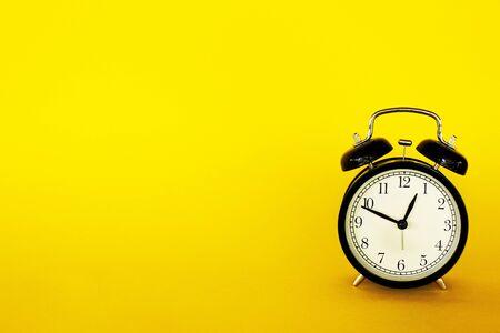 Retro style clock alarm clock on yellow background