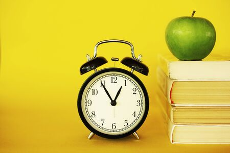 Retro style clock alarm clock on yellow background. Student brunch healthy meal