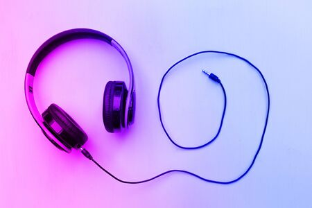 Headphones on neon background with free text space. Music concept.