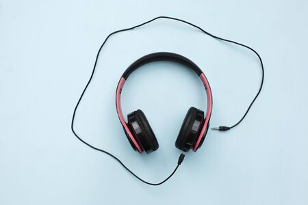 Headphones on blue background with free text space. Music concept.