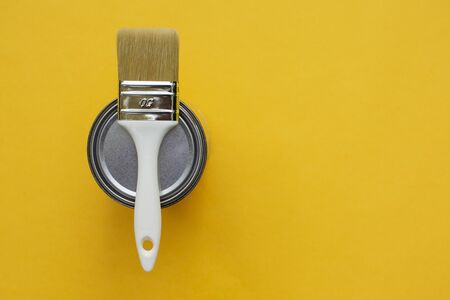 Brush on open can paint on yellow color background, self repair concept.