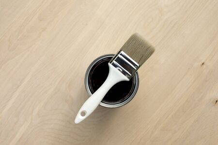 Brush on open can paint on wooden background, self repair concept.