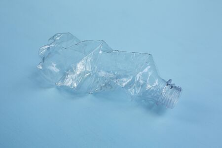Empty plastic bottle on blue background ecology concept