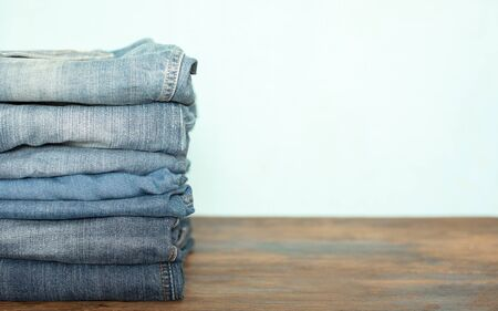Jeans trousers stack on rustic wooden background