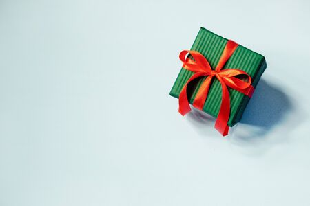 Green gift box with red ribbon on blue background