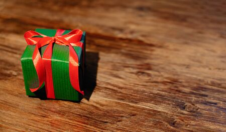 Green gift box with red ribbon on wooden background