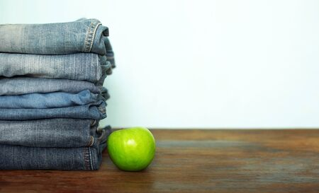 Jeans trousers stack on rustic wooden background with green apple Reklamní fotografie