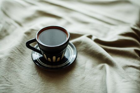 Cup of coffee on white bed background, vintage tone. Lifestyle concept.