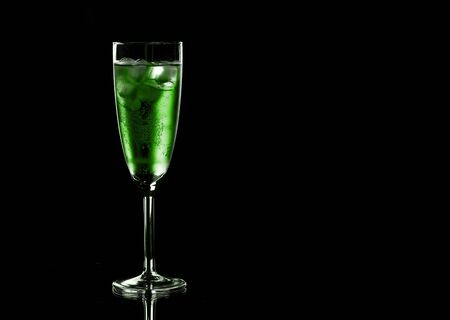 Glass of green champagne with ice on black background