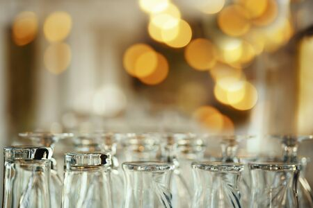 Empty glasses for beer on a bar rack waiting for the party
