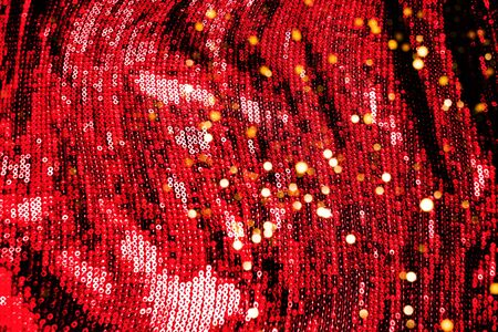 Cloth with flame scarlet paillettes. Background texture, new year and holiday, color trend 2020