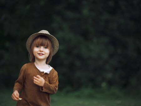 Little girl in a hat plays and laughs cheerfully in the woods