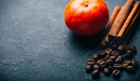 Coffee beans and cinnamon on black background with tangerine