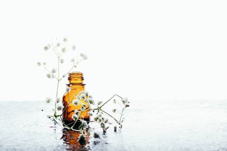 Natural cosmetics in water drops on white wooden table and dried flowers
