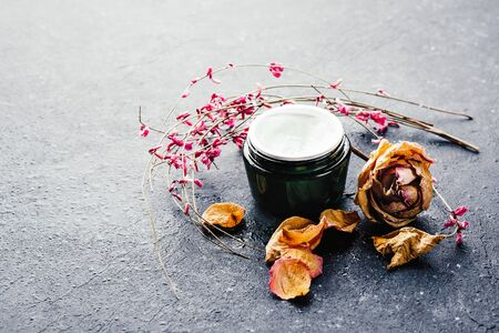 Natural cosmetics on black wooden table and dried flowers