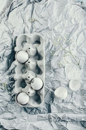 Easter eggs in a carton box, top view, spring flowers and freshen up