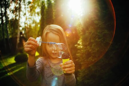 Girl blow bubbles, expectation of summer outdoor recreation, quarantine holiday