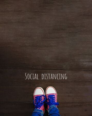 Legs in bright sneakers on wooden background. Social distancing, concept of staying physically apart for control spread of COVID-19