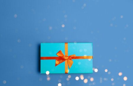 Green Christmas gift box on blue classic color background flat lay top view