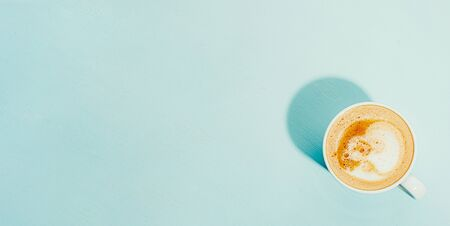 A cup of coffee on a blue background, top view flatlay