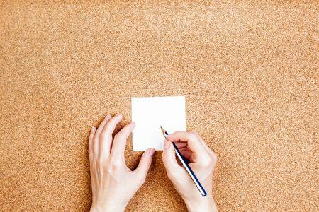Woman writes note on a cork background, memo list for store Archivio Fotografico - 150119109