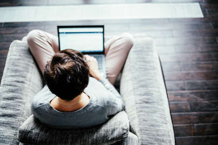 A woman works on a computer from home. Work from home in a comfortable chair, top view