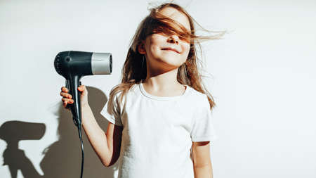 Girl in white t-shot dries her hair with a hair dryer