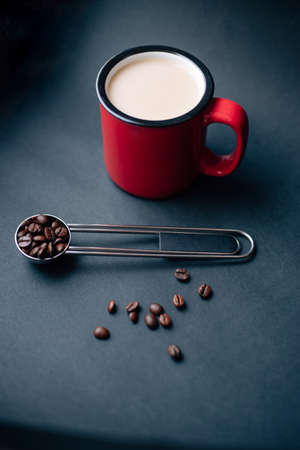 red cup withe coffee and silver spoon with coffee beans