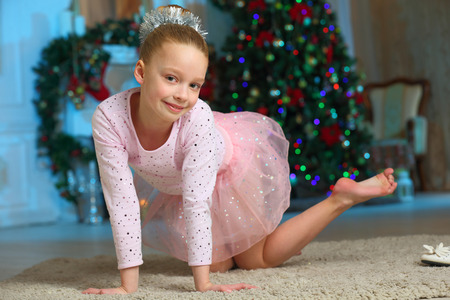 Pretty charming beautiful artistic blond baby girl in Christmas costumes. Beautiful blonde child girl in a New Years pink suit snowflakes.