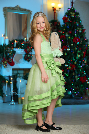 Beautiful charming pretty blond child-girl in a festive green dress with a favorite toy on the background of a New Year tree. Stock Photo