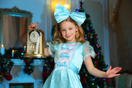 Pretty charming beautiful artistic blond baby girl in Christmas costumes. Beautiful blonde girl with a bow in a blue silk dress. 免版税图像
