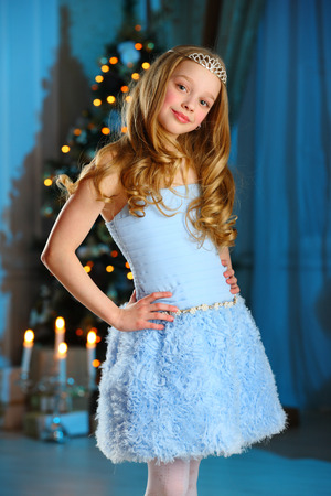 Beautiful blonde child girl in fairy princess costume on New Year's Eve. Lovely child in the background of a New Year tree.