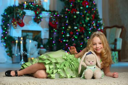 Mooi charmant mooi blond kind-meisje in een groene kleding met haar favoriete stuk speelgoed op de achtergrond van een nieuwe jaarboom. Stockfoto