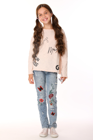 Pretty beautiful happy brunette young teen girl in blue jeans. The adorable slender smiling preteen standing in sports shoes. The image of children's summer fashion. Standard-Bild