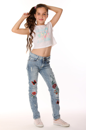 Pretty beautiful happy brunette young teen girl in blue jeans and a bare belly. The adorable slender smiling preteen standing in sports shoes. The image of childrens summer fashion. Stock Photo