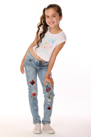 Pretty beautiful happy brunette young teen girl in blue jeans and a bare belly. The adorable slender smiling preteen standing in sports shoes. The image of children's summer fashion. Stock Photo