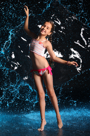 Adorable young teenage girl in a swimsuit stands barefoot in splashing water. Pretty child with dark hair, beautiful face and a slim figure. Slender preteen in a bikini. Banque d'images