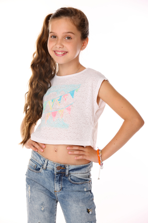 Portrait of beautiful happy brunette young teen girl in blue jeans and a bare belly. The adorable slender smiling preteen is an image of children's summer fashion.