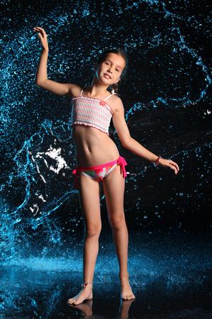 Adorable jeune adolescente en maillot de bain se tient pieds nus dans les éclaboussures d'eau. Joli enfant aux cheveux noirs, beau visage et silhouette mince. Préadolescent mince en bikini. Banque d'images - 93364144