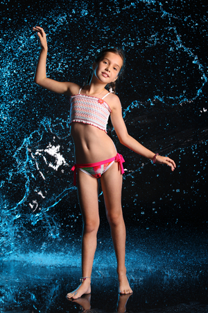 Adorable young teenage girl in a swimsuit stands barefoot in splashing water. Pretty child with dark hair, beautiful face and a slim figure. Slender preteen in a bikini. Stock Photo