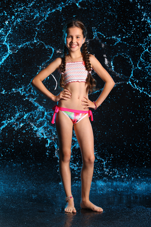 Happy young teenage girl in a swimsuit stands barefoot in splashing water. Pretty child with dark hair and beautiful face adorably smiles. Slender preteen in a bikini.