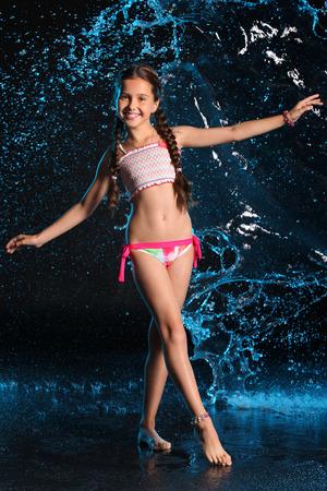 De gelukkige jonge tiener in een zwempak bevindt zich blootvoets in bespattend water. Mooi kind met donker haar en mooi gezicht adorably glimlacht. Slanke preteen in een bikini. Stockfoto - 93364146