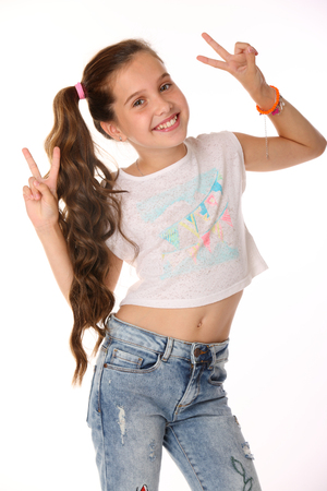 Portrait of beautiful happy brunette young teen girl in blue jeans and a bare belly. The adorable slender smiling preteen is an image of childrens summer fashion.