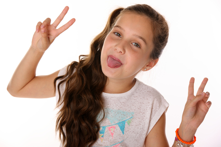 Portrait of beautiful cheerful brunette young teen girl builds a smiley face ape. The child playing tricks and shows tongue. Laughing preteen is an image of childrens summer fashion. Stock Photo