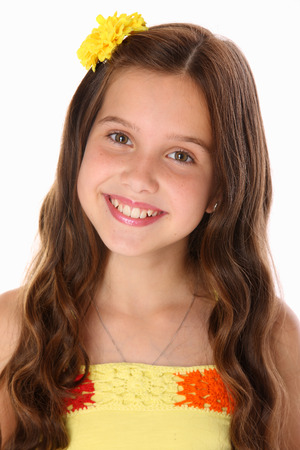 Portrait of a happy young teenage girl close-up. Pretty preteen with dark hair, charming face and bare shoulders smiles beautifully. The image of children's summer fashion.