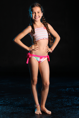 Happy young teenage girl in a swimsuit stands barefoot on a black background. Pretty child with dark hair and beautiful face adorably smiles. Slender preteen in a bikini. Stock Photo