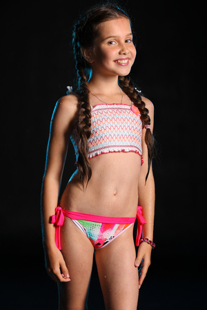 Portrait of a happy young teenage girl in a swimsuit. Pretty child with dark hair and beautiful face adorably smiles. Slender preteen in a bikini.