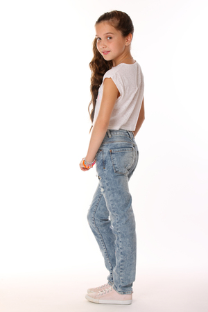Pretty beautiful brunette young teen girl in blue jeans. The adorable slender preteen standing on a white background in sports shoes. The image of childrens summer fashion. Stock Photo