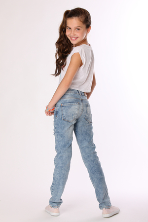 Pretty beautiful happy brunette young teen girl in blue jeans. The adorable slender smiling preteen standing in sports shoes. The image of children's summer fashion. Banque d'images