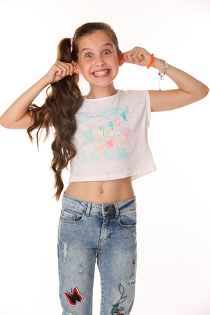 Portrait of beautiful cheerful brunette young teen girl builds a smiley face ape. The child playing tricks. Laughing preteen in blue jeans and a bare belly is an image of childrens summer fashion.